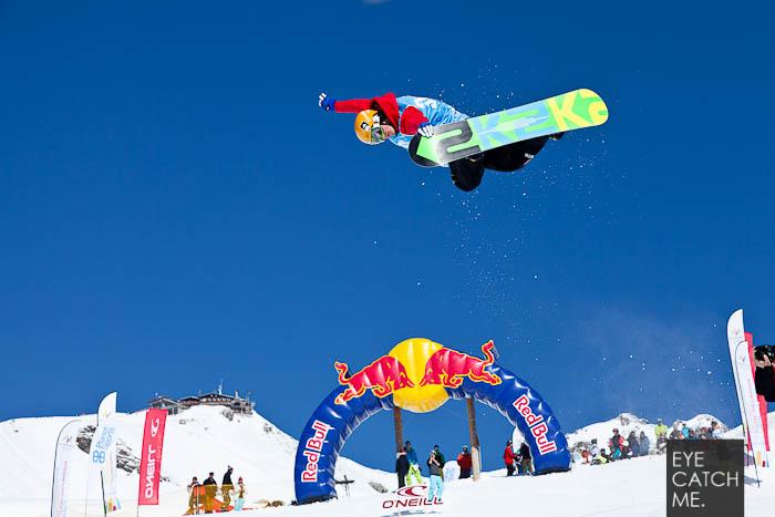 Das Foto zeigt einen Snowboarder der einen Backside Air in der Halfpipe macht, im Hintergrund ist ein großes Red Bull Logo zusehen