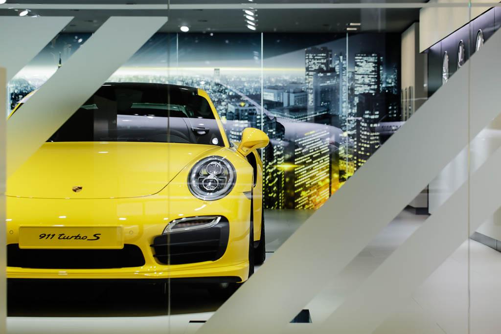 Standfoto der Porsche Exclusive Lounge auf der IAA, der schöne 911 Turbo in gelb lackiert, steht hinter einer Trennwand aus Glas