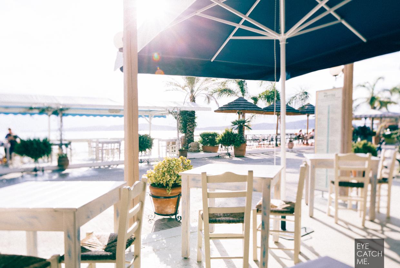 Griechisches Restaurant mit blauen Sonnenschirmen und weißen Stühlen von Fotograph EYECATCHME.
